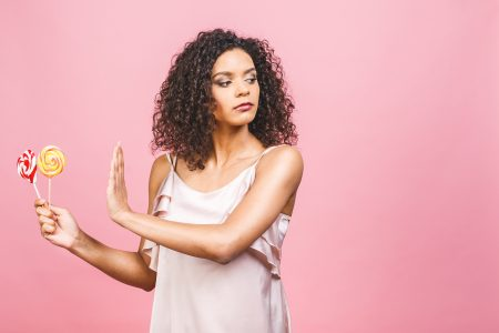 American afro girl does not eat cake. Conception to lose weight. Hand gesturing no to desserts. Isolated over pink background.