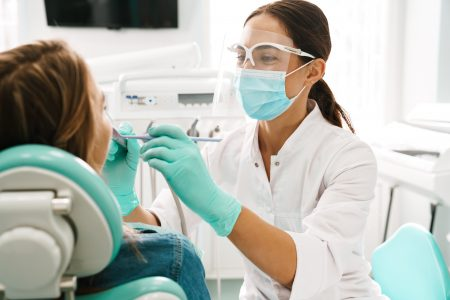 European mid pleased dentist woman in face mask working in dental clinic
